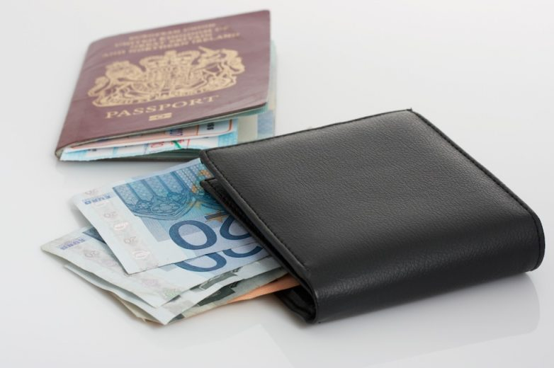 A passport and a wallet with euro bills